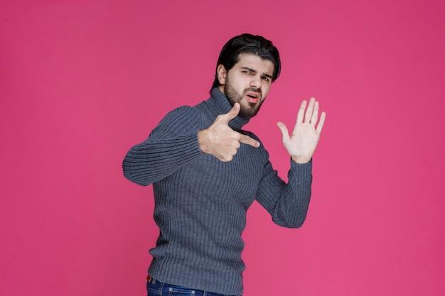Jeune homme aux cheveux longs et à la barbe montrant ou pointant quelque chose avec ses doigts.