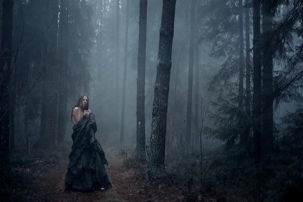 Jeune homme aux cheveux longs dans la forêt sombre