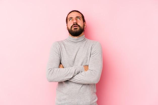 Jeune homme aux cheveux longs isolé sur fond rose fatigué d'une tâche répétitive.