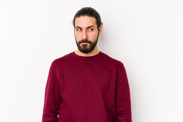 Jeune homme aux cheveux longs sur un mur blanc confus, se sent douteux et incertain.