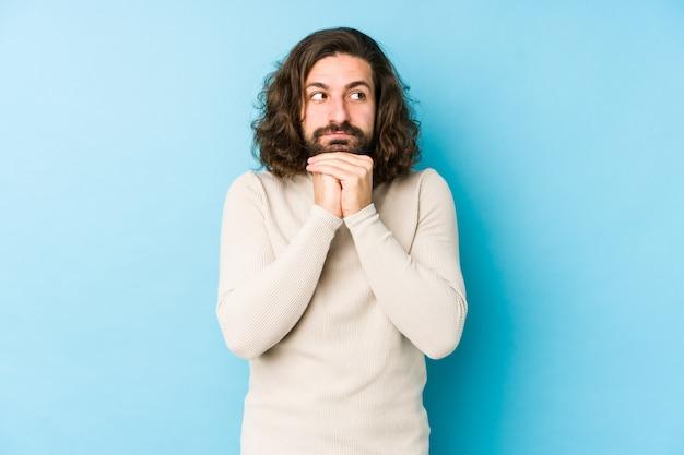 Un jeune homme aux cheveux longs sur un mur bleu garde les mains sous le menton, regarde joyeusement de côté.