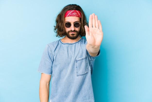 Jeune homme aux cheveux longs portant un look hipster festival debout avec la main tendue montrant le panneau d'arrêt