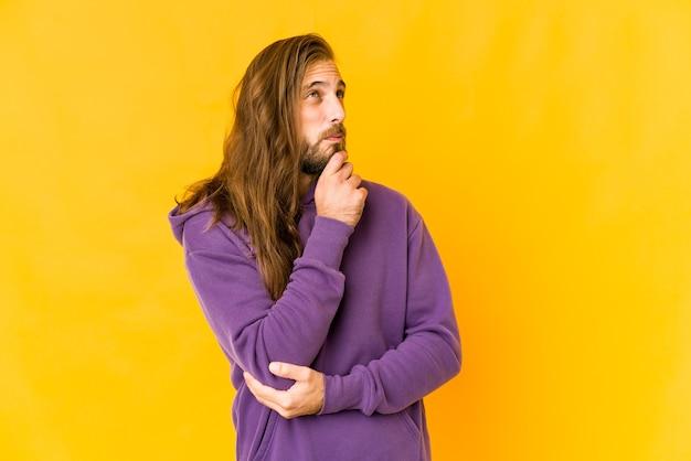 Jeune homme aux cheveux longs regarde sur le côté avec une expression douteuse et sceptique.