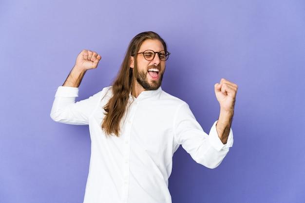Jeune homme aux cheveux longs regarde lever le poing après une victoire, concept gagnant