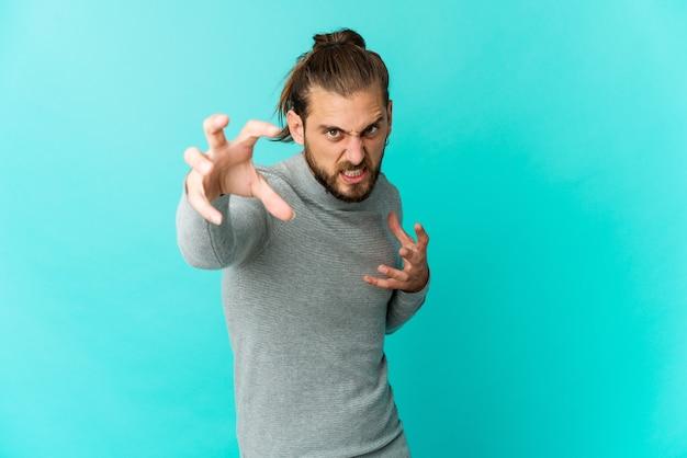 Jeune homme aux cheveux longs regarde montrant des griffes imitant un chat, geste agressif.