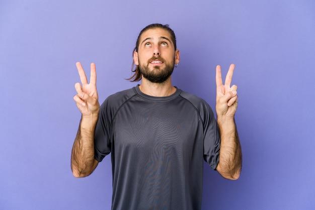 Jeune homme aux cheveux longs regarde sourire, pointant du doigt la bouche.