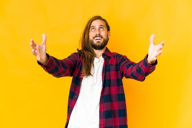 Un jeune homme aux cheveux longs semble célébrer une victoire ou un succès, il est surpris et choqué.