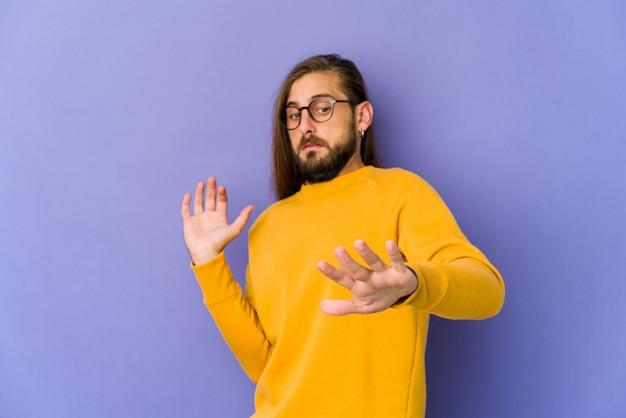 Jeune homme aux cheveux longs semble choqué en raison d'un danger imminent