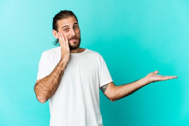 Un jeune homme aux cheveux longs tient un espace de copie sur une paume, gardez la main sur la joue. émerveillé et ravi.