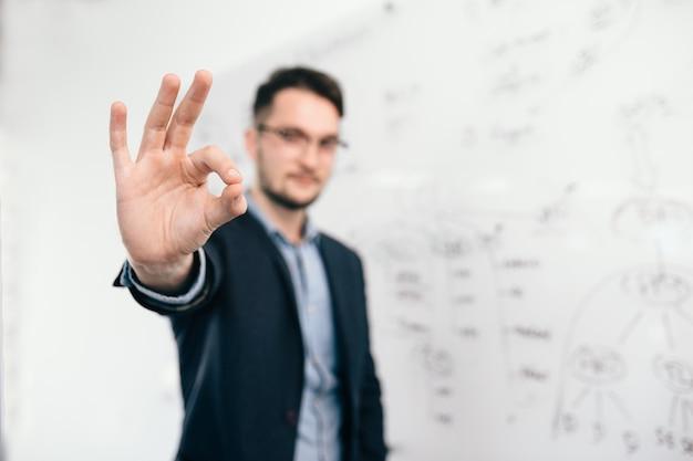 Jeune homme aux cheveux noirs à lunettes est debout près du tableau blanc au bureau. il porte une chemise bleue et une veste sombre. concentrez-vous sur l'avant sur son signe avec la main.