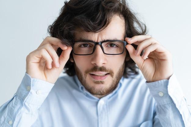 Jeune homme aux cheveux noirs surpris regardant la caméra