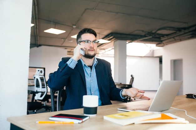 Jeune homme aux cheveux noirs travaille à la table au bureau. il porte une chemise bleue avec une veste noire. il parle au téléphone et semble perdu.