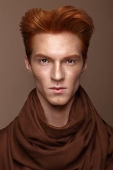Jeune homme aux cheveux roux et maquillage créatif et cheveux.