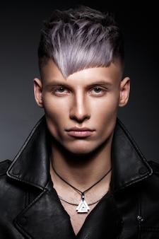 Jeune homme aux cheveux violets et maquillage créatif et cheveux.