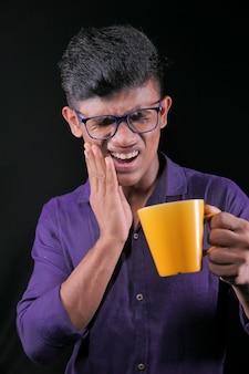 Jeune homme aux dents sensibles et verre d'eau froide.