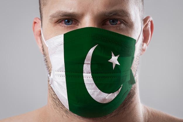 Jeune homme aux yeux endoloris dans un masque médical peint aux couleurs du drapeau national du pakistan. protection médicale contre les maladies aéroportées, coronavirus. l'homme a peur de contracter la grippe