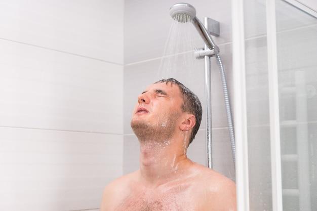 Jeune homme aux yeux fermés prenant une douche, debout sous l'eau qui coule dans la cabine de douche avec portes en verre transparent dans la salle de bain
