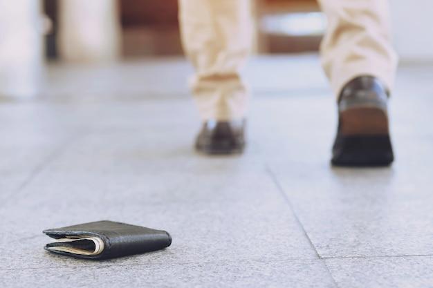 Le jeune homme avait perdu son portefeuille en cuir avec de l'argent dans la rue. gros plan du portefeuille allongé sur le trottoir en béton de la route pendant le voyage pour voyager. avec filtre tons effet chaud rétro vintage.