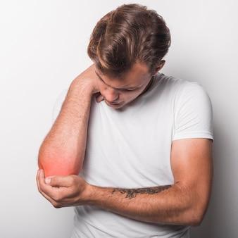 Jeune homme ayant une blessure au coude debout sur fond blanc