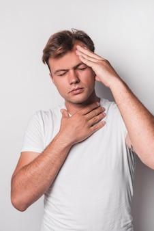 Jeune homme ayant des maux de tête sur fond blanc