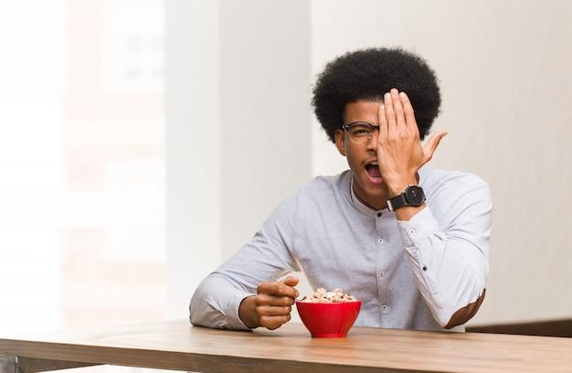 Jeune homme ayant un petit déjeuner en criant heureux et couvrant le visage avec la main
