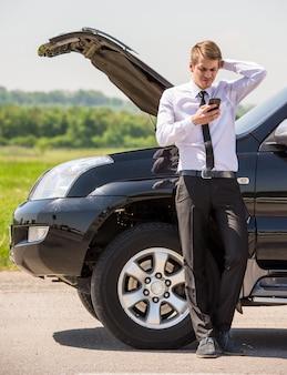 Jeune homme ayant des problèmes avec sa voiture cassée.