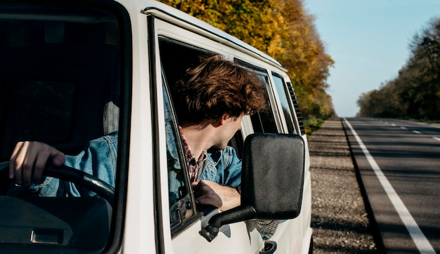 Jeune homme ayant un roadtrip dans sa camionnette