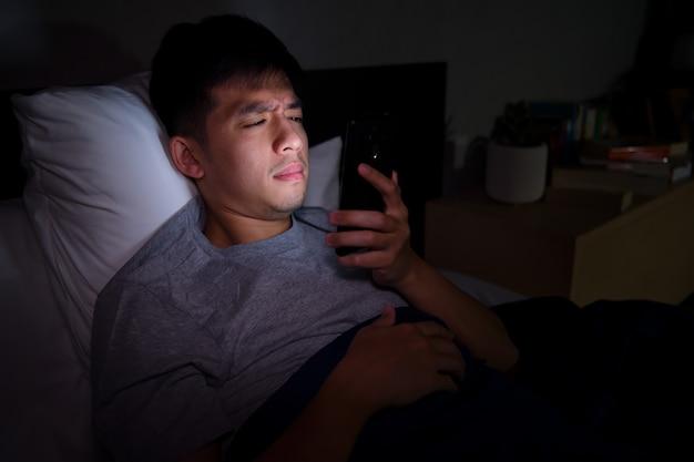 Jeune homme ayant les yeux endoloris et fatigués lors de l'utilisation de smartphone en position couchée dans son lit la nuit