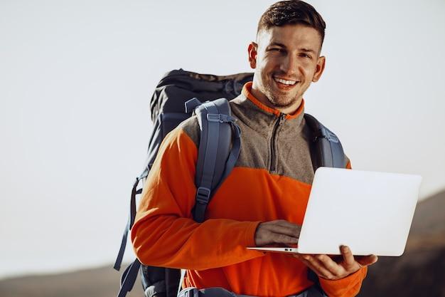Jeune homme backpacker à l'aide de son ordinateur portable en voyage en montagne
