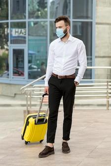 Jeune homme, à, bagages, porter, masque