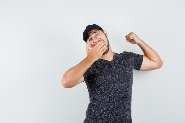 Jeune homme bâillant et s'étendant en t-shirt et casquette et à la somnolence