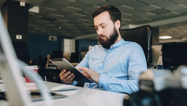 Jeune homme à la barbe à l'aide d'une tablette tout en travaillant sur son lieu de travail