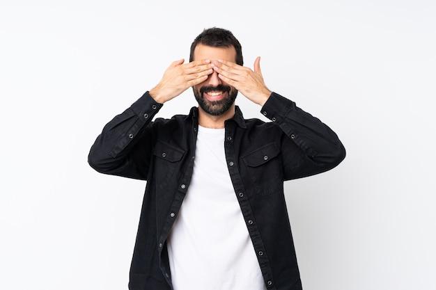 Jeune homme à la barbe sur blanc isolé couvrant les yeux par les mains