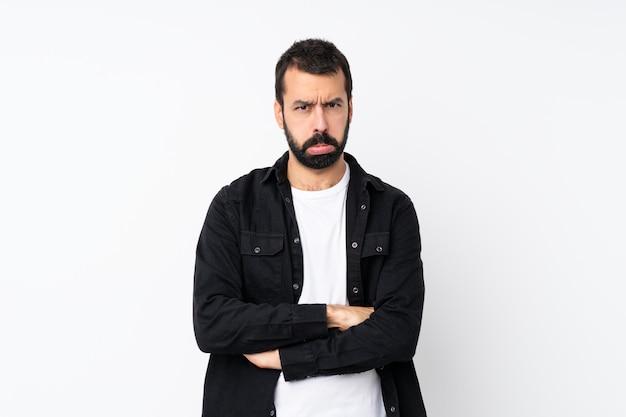 Jeune homme à la barbe sur blanc isolé avec une expression triste et déprimée