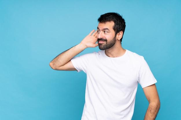 Jeune homme à la barbe sur bleu isolé, écoutant quelque chose en mettant la main sur l'oreille