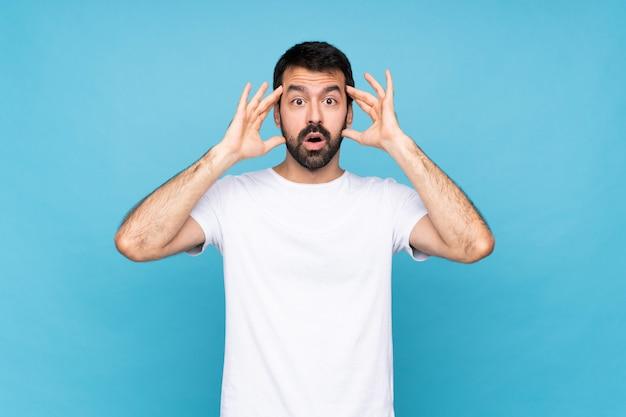 Jeune homme à la barbe sur bleu isolé avec une expression de surprise