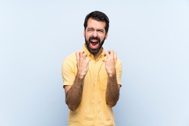 Jeune homme à la barbe sur bleu isolé frustré par une mauvaise situation