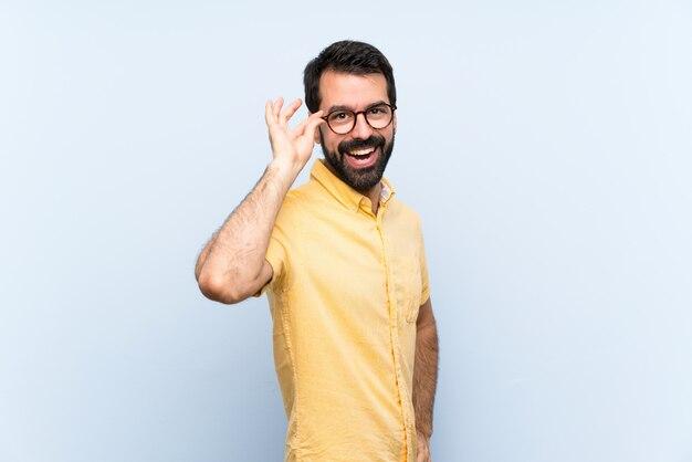 Jeune homme à la barbe sur bleu isolé avec des lunettes et souriant