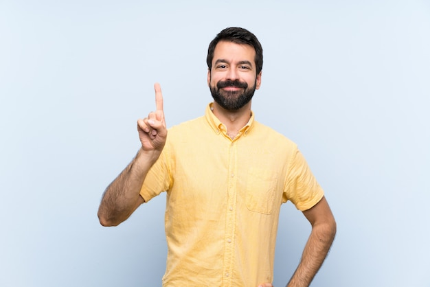 Jeune homme à la barbe sur bleu isolé montrant et en levant un doigt en signe du meilleur