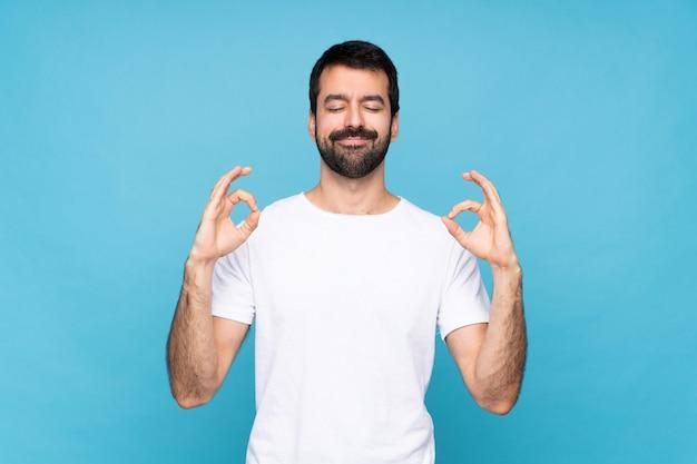 Jeune homme à la barbe sur bleu isolé en pose zen