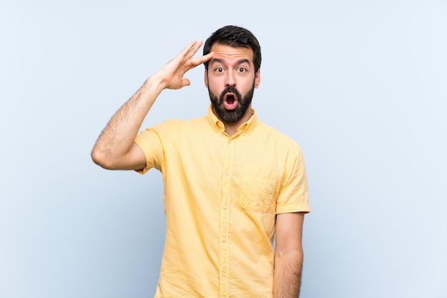 Jeune homme à la barbe sur bleu isolé vient de réaliser quelque chose et a l'intention de la solution