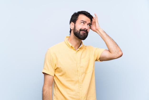 Jeune homme à la barbe sur bleu isolé