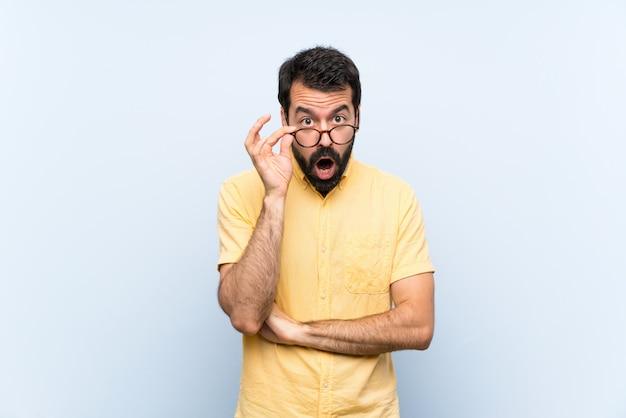Jeune homme à la barbe sur bleu avec des lunettes et surpris