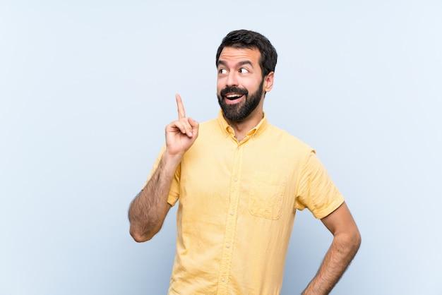 Jeune homme à la barbe sur bleu pensant une idée pointant le doigt vers le haut