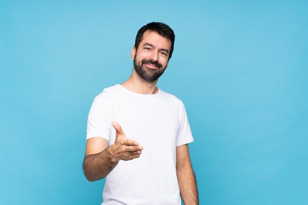 Jeune homme avec barbe sur bleu se serrant la main pour fermer une bonne affaire