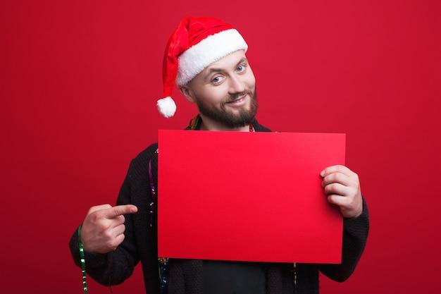 Jeune homme avec barbe et chapeau de nouvel an pointe vers un espace vide rouge sur une bannière tenant sur un mur de studio