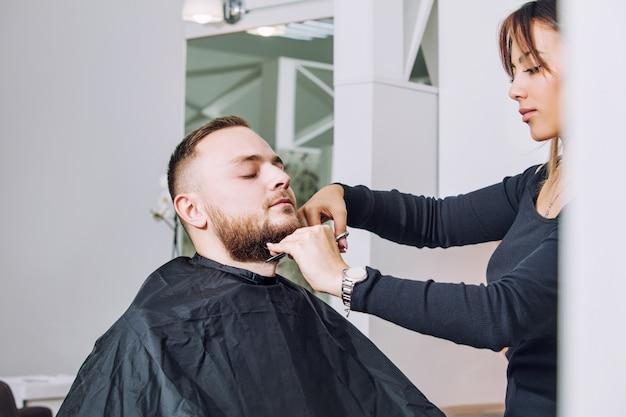 Jeune homme avec une barbe sur une coupe de cheveux et une conception de barbe chez le coiffeur dans le salon de beauté