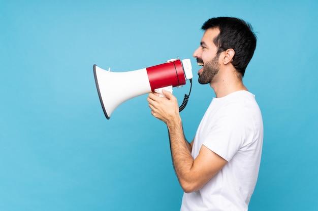 Jeune homme à la barbe criant dans un mégaphone