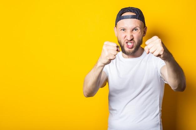 Jeune homme avec une barbe dans une casquette de baseball avec les poings fermés veut frapper