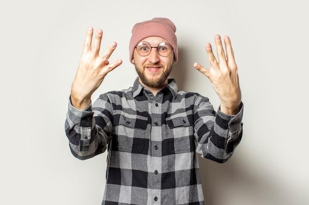Jeune homme avec une barbe dans un chapeau, une chemise à carreaux étendit ses bras devant lui avec le dos de sa main sur un blanc isolé. arrêtez le geste, assez